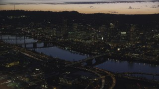 AX155_298 - 6K stock footage aerial video of a reverse view of downtown skyscrapers, Willamette River bridges, and freeway interchange at night, Downtown Portland, Oregon