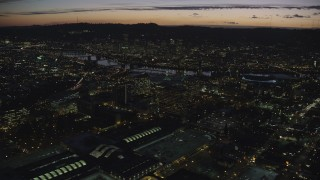 AX155_299 - 6K stock footage aerial video approaching office buildings, convention center, the Willamette River, and Downtown Portland at night in Oregon