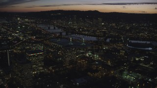AX155_300 - 6K stock footage aerial video flying over convention center to approach the Willamette River and Downtown Portland at night in Oregon