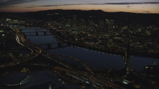 AX155_301 - 6K stock footage aerial video crossing the Willamette River to approach Burnside Bridge, White Stag Sign, and Downtown Portland at night in Oregon