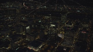 AX155_306 - 6K stock footage aerial video flying by Park Avenue West Tower and Fox Tower at night in Downtown Portland, Oregon, tilt to city streets