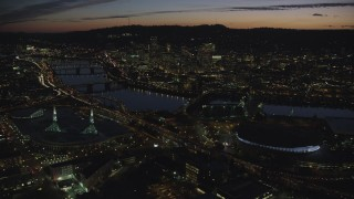 AX155_308 - 6K stock footage aerial video of Downtown Portland and Willamette River at night seen from Moda Center in Oregon