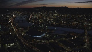 AX155_309 - 6K stock footage aerial video of Downtown Portland and Willamette River at night seen from Moda Center and Memorial Coliseum in Oregon