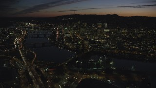 AX155_314 - 6K stock footage aerial video of a view of Downtown Portland, Oregon, at night across the Willamette River