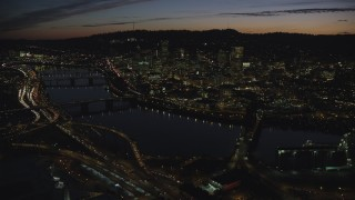AX155_315 - 6K stock footage aerial video of a view across the Willamette River of Downtown Portland, Oregon, at night