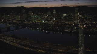 AX155_318 - 6K stock footage aerial video of Downtown Portland skyscrapers at night seen across the Willamette River, Oregon