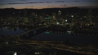 AX155_319 - 6K stock footage aerial video of Downtown Portland skyscrapers at night seen across the Morrison Bridge and Willamette River, Oregon