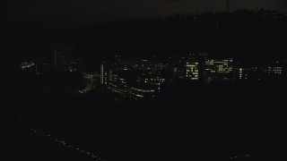 AX155_358 - 6K stock footage aerial video flying by and away from the Oregon Health and Science University at night in Portland, Oregon