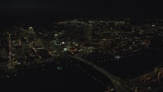 AX155_360 - 6K stock footage aerial video of Downtown Portland, the Morrison Bridge and the Burnside Bridge over Willamette River, night, Oregon