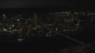 AX155_361 - 6K stock footage aerial video of US Bancorp Tower and the White Stag sign across the Willamette River and Burnside Bridge, night, Downtown Portland, Oregon