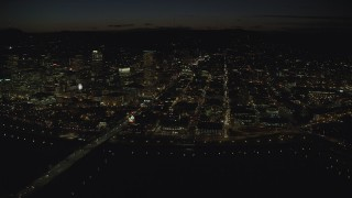 AX155_362 - 6K stock footage aerial video of US Bancorp Tower and White Stag sign across the Willamette River, Burnside Bridge and Steel Bridge, night, Downtown Portland, Oregon