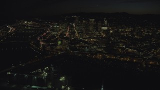 AX155_364 - 6K stock footage aerial video flying by then approaching downtown skyscrapers by bridges over the Willamette River at nighttime, Downtown Portland, Oregon