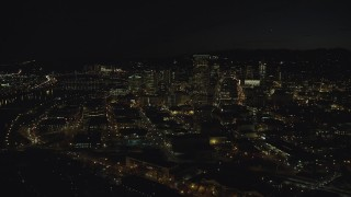 AX155_365 - 6K stock footage aerial video approaching US Bancorp Tower and skyscrapers by the Willamette River at nighttime, Downtown Portland, Oregon