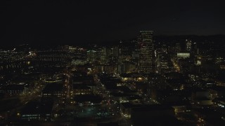 AX155_366 - 6K stock footage aerial video of US Bancorp Tower and skyscrapers by the Willamette River at nighttime, Downtown Portland, Oregon