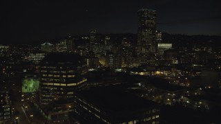 AX155_368 - 6K stock footage aerial video flying by One Pacific Square, with US Bancorp Tower and high-rises in the background at night, Downtown Portland, Oregon