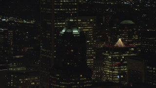 AX155_375 - 6K stock footage aerial video of KOIN Center rooftop venting steam at night in Downtown Portland, Oregon