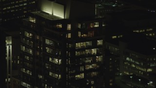 AX155_384 - 6K stock footage aerial video of offices on top floors of Park Avenue West Tower at night in Downtown Portland, Oregon