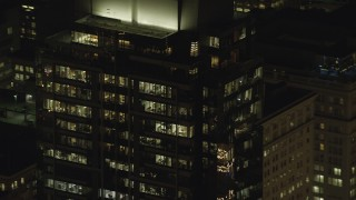 AX155_385 - 6K stock footage aerial video of the top floors of Park Avenue West Tower at night in Downtown Portland, Oregon