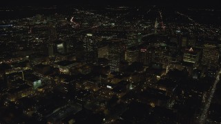 AX155_401 - 6K stock footage aerial video passing downtown high-rises, skyscrapers, and busy streets at nighttime in Downtown Portland, Oregon