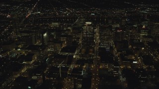 AX155_402 - 6K stock footage aerial video flying by and approaching downtown high-rises, skyscrapers, and busy streets at nighttime in Downtown Portland, Oregon