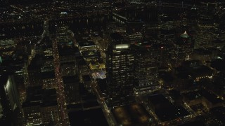 AX155_403 - 6K stock footage aerial video flying over skyscrapers to reveal Christmas tree in Pioneer Courthouse Square at night in Downtown Portland, Oregon