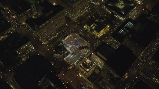 AX155_404 - 6K stock footage aerial video orbiting and flying away from Christmas tree in Pioneer Courthouse Square at night in Downtown Portland, Oregon