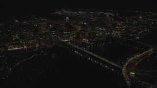 AX155_406 - 6K stock footage aerial video flying by and approaching Downtown Portland from the Hawthorne Bridge at night, Oregon