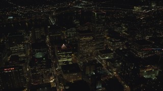 AX155_414 - 6K stock footage aerial video flying by PacWest Center, SW Jefferson Street, and Wells Fargo Center at night in Downtown Portland, Oregon