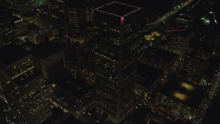 AX155_415 - 6K stock footage aerial video orbiting Wells Fargo Center to reveal busy city streets and KOIN Center at night in Downtown Portland, Oregon