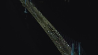 AX155_418 - 6K stock footage aerial video tracking and a reverse view of a commuter train crossing the Tilikum Crossing bridge at night in South Portland, Oregon