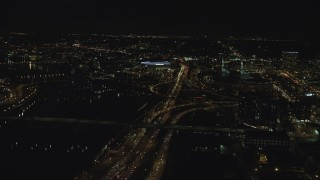 AX155_420 - 6K stock footage aerial video following I-5 over interchange to approach Moda Center and convention Center at night in Northeast Portland, Oregon