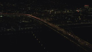 AX155_425 - 6K stock footage aerial video orbiting the Fremont Bridge with heavy traffic on upper deck to reveal Downtown Portland, Oregon