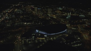 AX155_430 - 6K stock footage aerial video flying by Moda Center and office buildings at night in Northeast Portland, Oregon