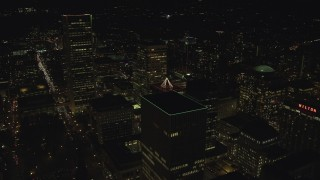 AX155_434 - 6K stock footage aerial video flying over skyscrapers to reveal and approach Portland State University at night, Downtown Portland, Oregon