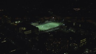 AX155_435 - 6K stock footage aerial video approaching football practice at Portland State University sports field at night, Downtown Portland, Oregon