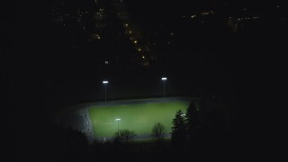 AX155_443 - 6K stock footage aerial video approaching and flying over high school soccer field at night, Southwest Portland, Oregon