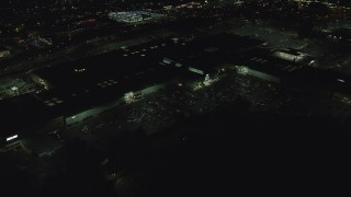 AX155_454 - 6K stock footage aerial video orbiting the side of Washington Square shopping mall at night in Tigard, Oregon