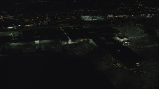 AX155_455 - 6K stock footage aerial video orbiting side of Washington Square mall at night in Tigard, Oregon