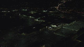 AX155_456 - 6K stock footage aerial video orbiting the side of Washington Square mall at nighttime in Tigard, Oregon