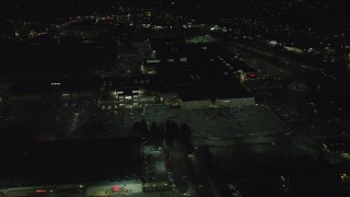 AX155_457 - 6K stock footage aerial video orbiting around the side of Washington Square mall at nighttime in Tigard, Oregon