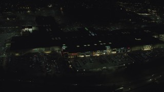 AX155_459 - 6K stock footage aerial video orbiting around Washington Square shopping mall at nighttime in Tigard, Oregon