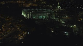AX155_469 - 6K stock footage aerial video flying by six-story parking garage at night, Beaverton, Oregon