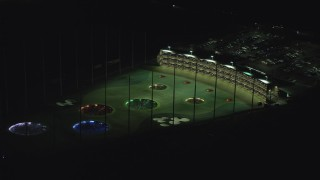 AX155_476 - 6K stock footage aerial video slowly flying by a Topgolf course in Hillsboro, Oregon at night