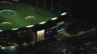 AX155_483 - 6K stock footage aerial video flying away from the Topgolf course in Hillsboro, Oregon at night