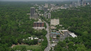 AX36_049 - 5K stock footage aerial video following Peachtree Road past office buildings among wooded area, Buckhead