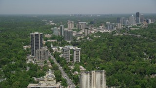 AX36_050 - 5K stock footage aerial video following Peachtree Road past office buildings and wooded area, Buckhead