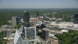 AX36_069 - 5K stock footage aerial video flying by skyscrapers and office buildings toward a shopping center, Buckhead, Georgia