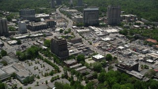 AX36_077 - 5K stock footage aerial video following a road by office buildings toward downtown skyscrapers, Buckhead, Georgia