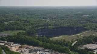 AX37_086 - 5K stock footage aerial video approaching a quarry bordering a wooded area, Atlanta, Georgia