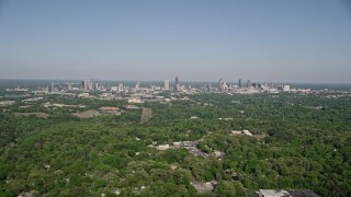 AX38_003 - 5K stock footage aerial video flying over forests toward Midtown and Downtown Atlanta, Georgia